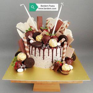 Naked cake tarzında, üzeri çikolata, gofret gibi atıştırmalıklarla sülenmiş doğum günü pastası